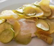 Filetti di pesce in un letto di patate e zucchine